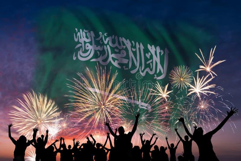 Os povos estão olhando em fogos-de-artifício e em bandeira de Arábia Saudita foto de stock