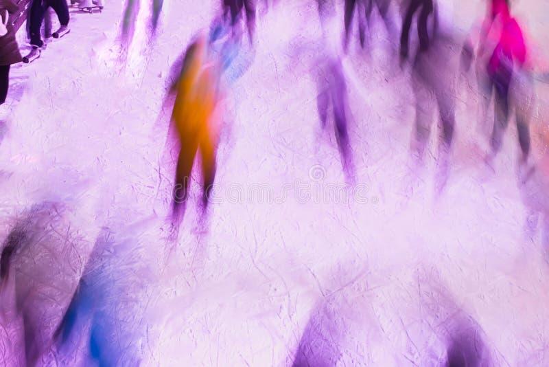 Os povos estão patinando no parque na pista do inverno, borrão de movimento Natal, esporte, estilo de vida saudável imagens de stock