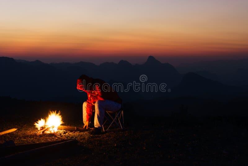 Os povos estão pondo a madeira no fogo imagens de stock