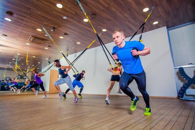 Os povos fazem fitnes exercitar com uma faixa no gym imagens de stock