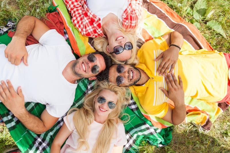Os povos felizes agrupam os amigos novos que encontram-se para baixo na cobertura do piquenique exterior imagem de stock