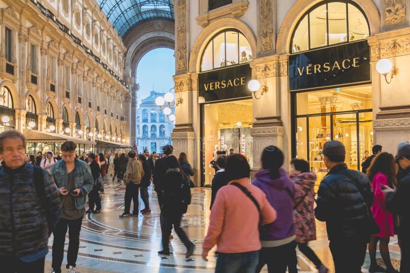 Os povos felizes andam na frente das lojas luxuosas em Milão imagens de stock