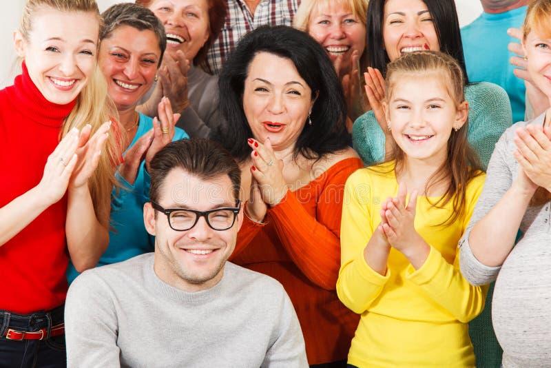Os povos felizes aplaudem suas mãos. imagens de stock royalty free