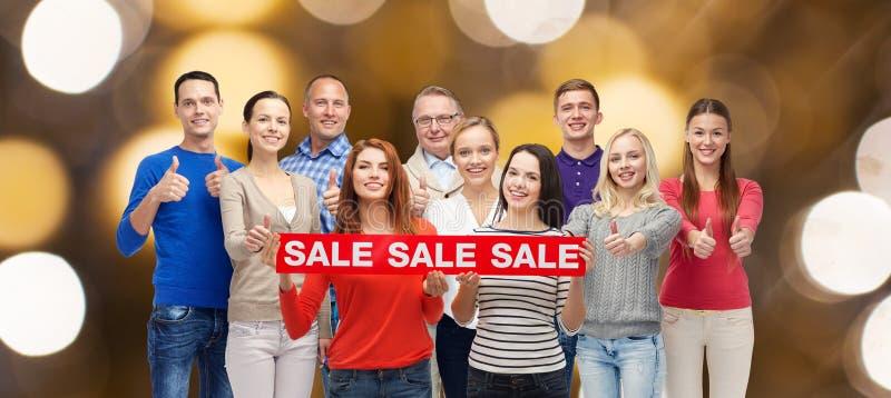 Os povos felizes com venda assinam mostrar os polegares acima fotografia de stock royalty free