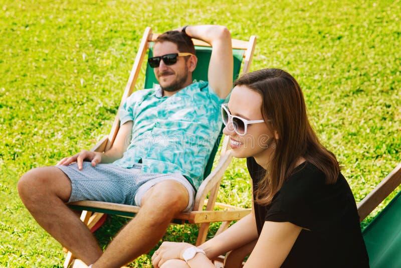 Os povos felizes que relaxam e comunicam exterior no relaxamento feliz da jovem mulher do fundo exterior foto de stock