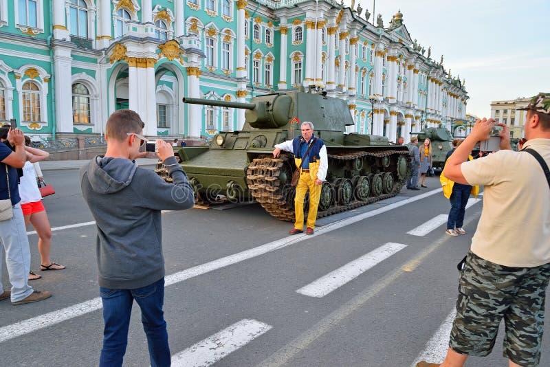 Os povos fotografaram contra o contexto do tanque pesado soviético quilovolt fotografia de stock royalty free