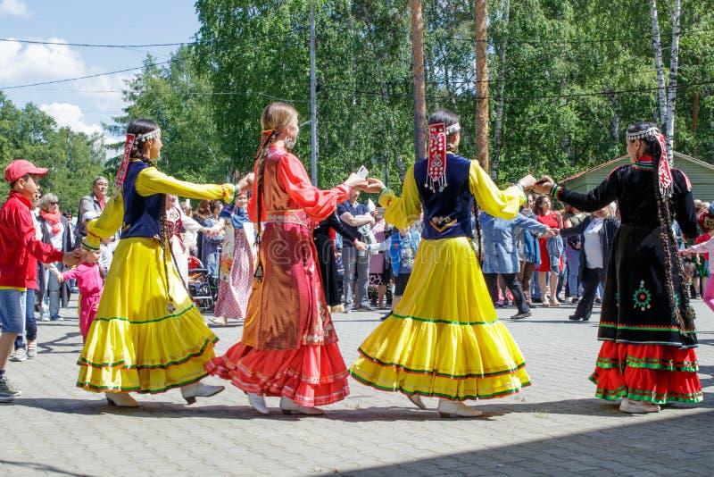 Os povos guardam as mãos, dançando em um círculo O feriado nacional anual dos Tatars e dos Bashkirs Sabantuy no parque da cidade foto de stock royalty free