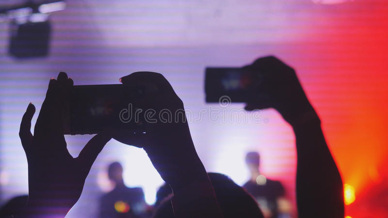 Os povos guardam o telefone esperto e o concerto de registros Multidão que partying em um concerto fotos de stock royalty free