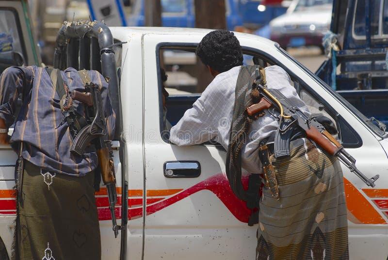Os povos iemenitas com as metralhadoras do Kalashnikov falam a um motorista em Aden, Iémen fotografia de stock royalty free