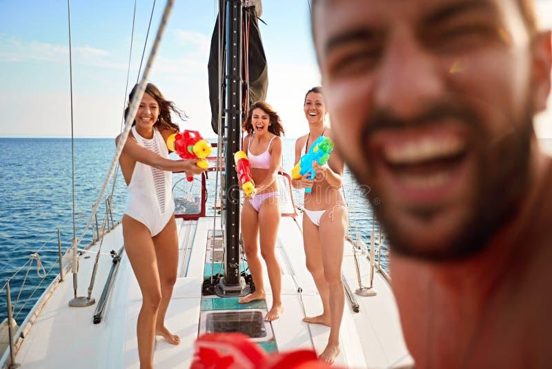 Os povos jogam no barco de navigação com as pistolas de água em férias imagens de stock