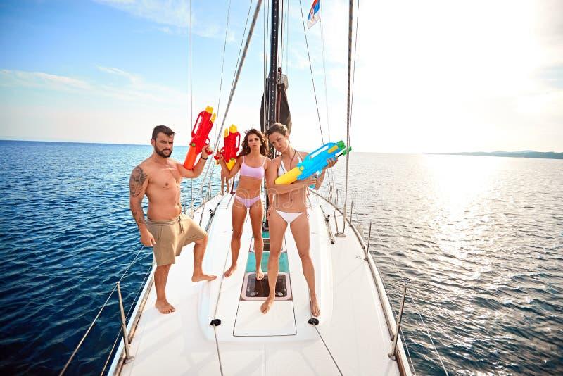 Os povos jogam no barco de navigação com as pistolas de água em férias imagem de stock