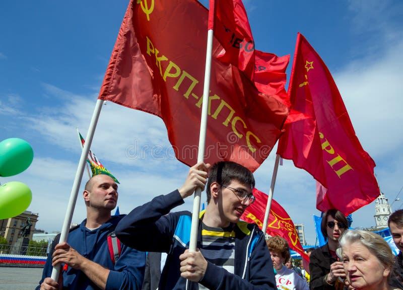 Os povos levam bandeiras vermelhas na demonstração do primeiro de maio fotos de stock royalty free