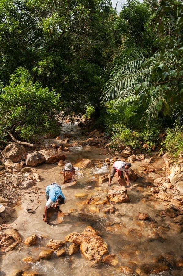 Os povos locais fazem a filtração do ouro ou da lata em um rio em Tailândia fotos de stock royalty free
