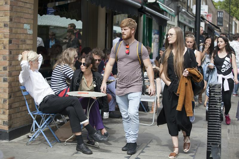 Os povos locais sentam-se em uma tabela em cafés da rua durante um mercado na estrada de Broadway A multidão heterogêneo vagueia  fotografia de stock royalty free