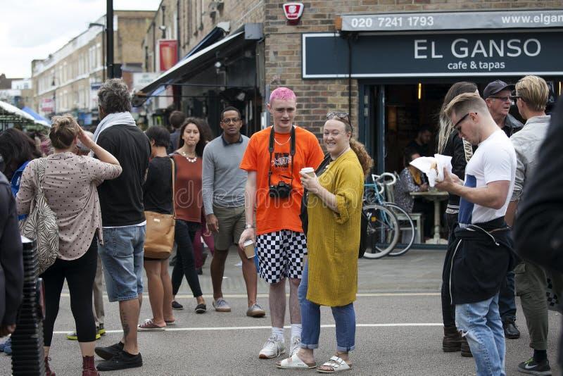 Os povos locais sentam-se em uma tabela em cafés da rua durante um mercado na estrada de Broadway A multidão heterogêneo vagueia  imagens de stock