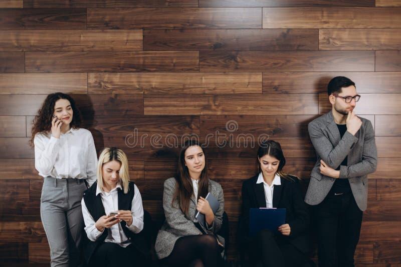 os povos milenares Multi-étnicos que guardam telefones e os resumos que preparam-se para a entrevista de trabalho, candidatos div fotos de stock