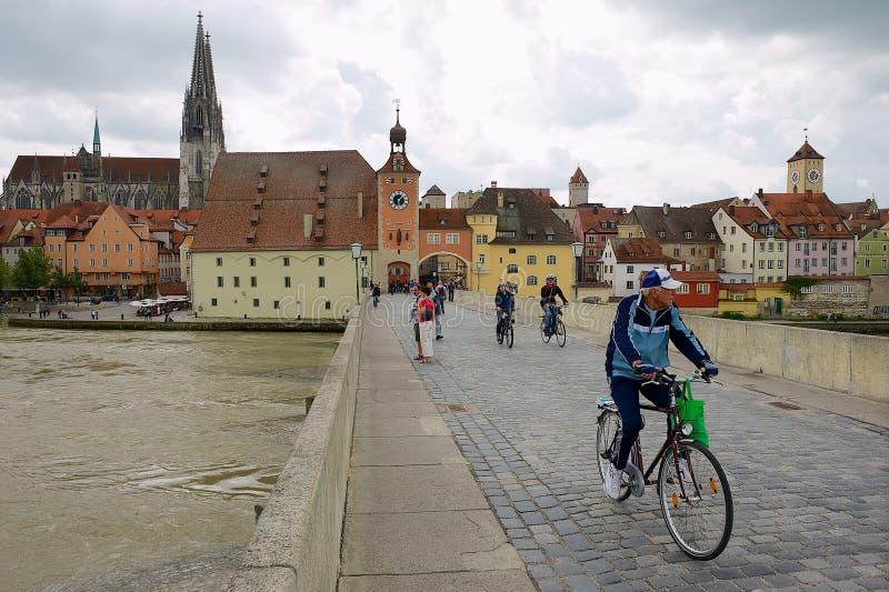 Os povos montam bicicletas pela ponte de pedra em Regensbusg, Alemanha fotografia de stock
