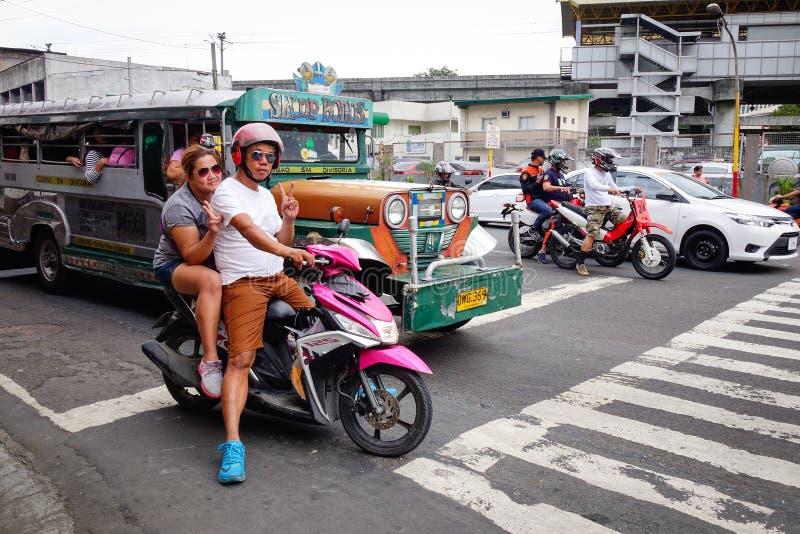 Os povos montam 'trotinette's na rua em Manila, Filipinas fotografia de stock