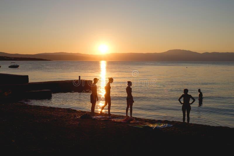 Os povos mostram em silhueta no por do sol em Malinska, ilha de Krk, Croácia imagens de stock royalty free