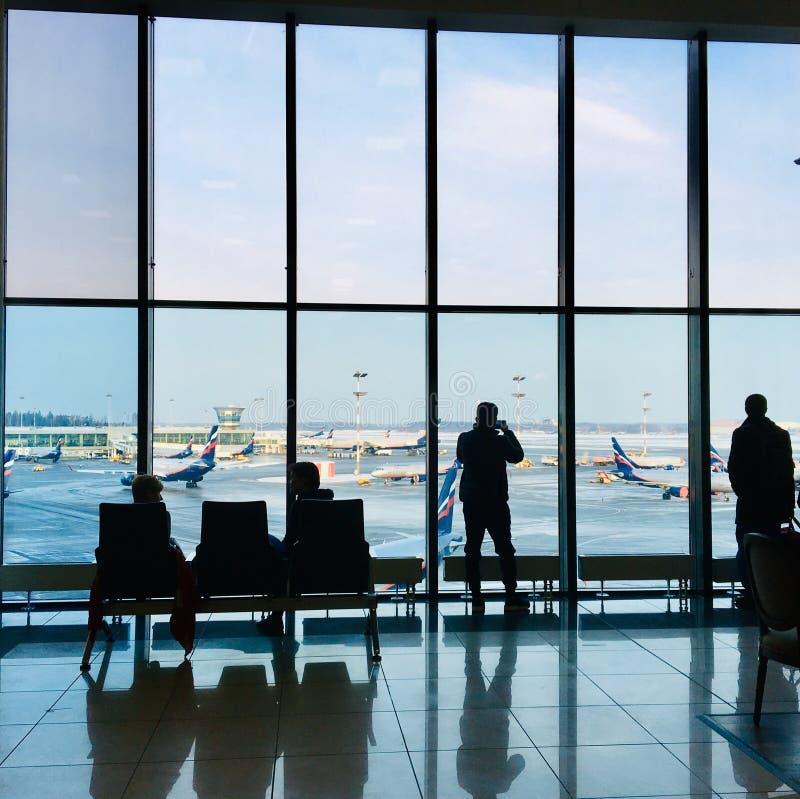 Os povos mostram em silhueta no terminal de aeroporto imagens de stock