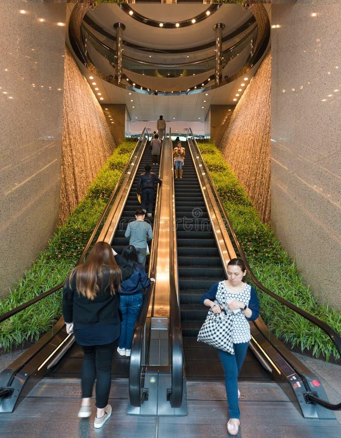 Os povos movem-se em escadas rolantes no quadrado de duas trocas fotos de stock