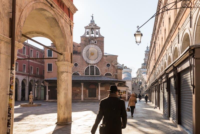 Os povos não identificados andam perto da igreja de San Giacomo di Rialto ou de Chiesa di San Giacomo di Rialto em Veneza imagens de stock