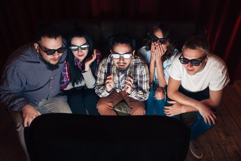 Os povos nos vidros 3d olham a tevê, surpreendida por efeitos fotografia de stock royalty free