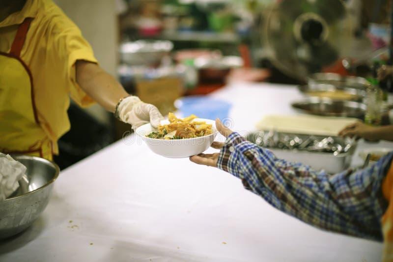 Os povos pobres recebem o alimento doado dos doadores, demonstram a partilha mútua na sociedade de hoje: o conceito de ajudar o c fotografia de stock royalty free