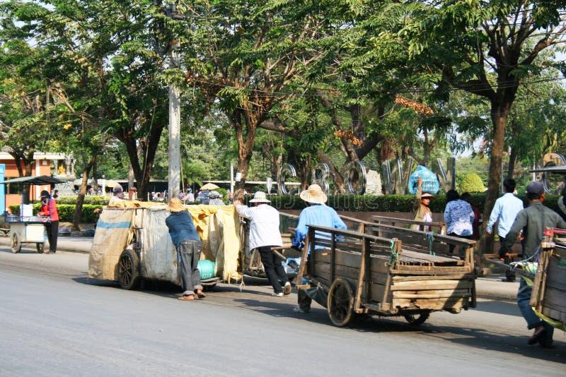 Os povos puxam carros na estrada em Tailândia. imagens de stock royalty free