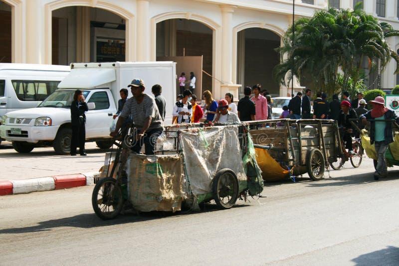 Os povos puxam carros na estrada em Tailândia. foto de stock