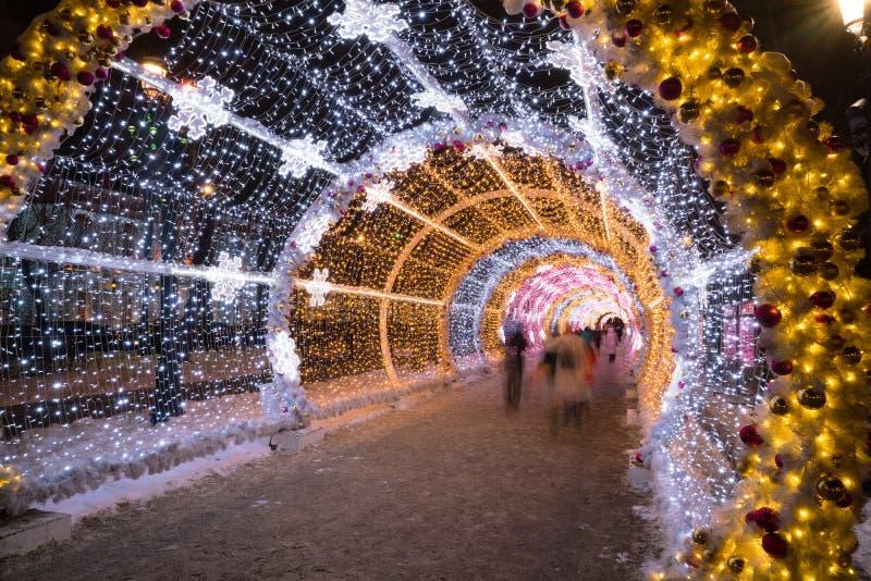 Os povos que andam com luz dos feriados do ano novo e do Natal escavam um túnel no centro da cidade em Moscou foto de stock royalty free