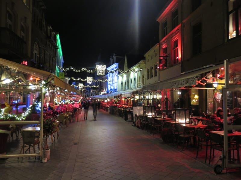 Os povos que andam no Natal brilhantemente iluminado decoraram ruas fotos de stock royalty free