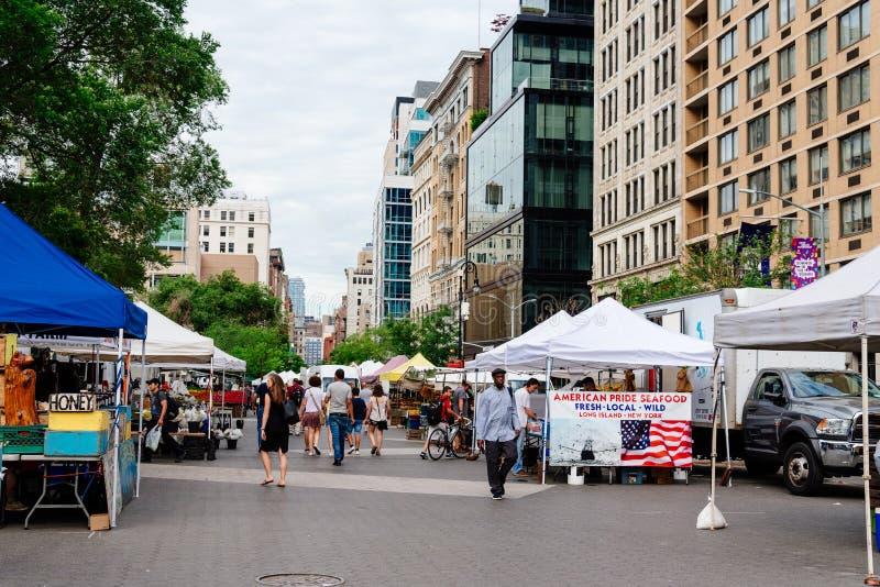Os povos que andam pelo mercado param em Union Square Greenmarket em N foto de stock