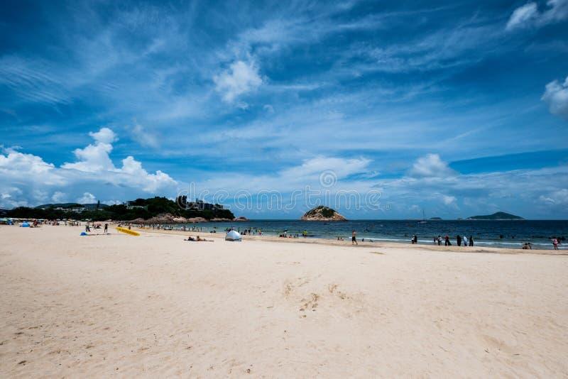 Os povos que apreciam o sol brilham na praia na tarde ensolarada foto de stock