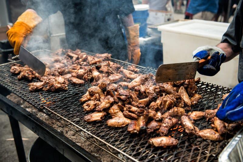 Os povos que cozinham as asas e os pés de galinha no assado grelham o festival do alimento da rua fora imagem de stock royalty free