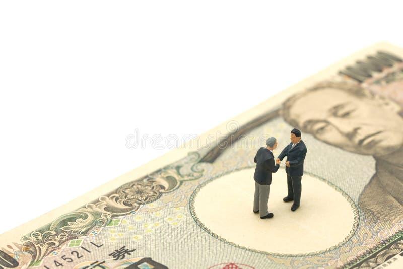 Os povos que da miniatura 2 os homens de negócios agitam as mãos estão no valor japonês das cédulas 10.000 ienes usando-se como o imagem de stock