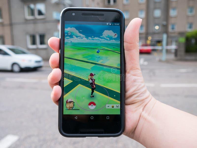 Os povos que jogam Pokemon VÃO o telefone esperto aumentado batida app da realidade imagem de stock