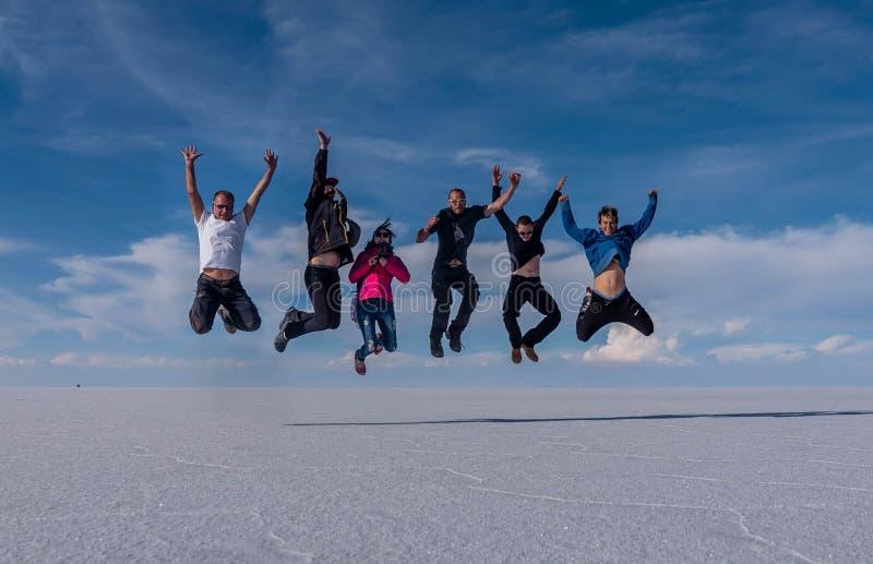 Os povos que saltam no lago Salar de Uyuni, Bolívia imagens de stock