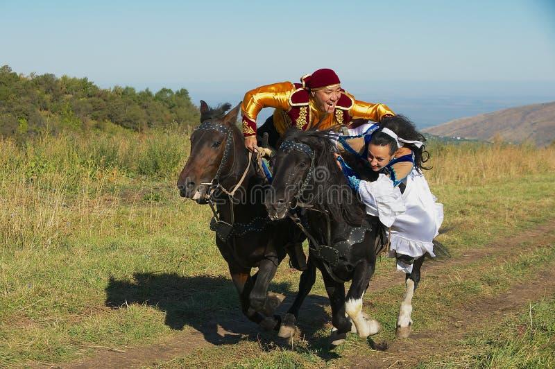 Os povos que vestem vestidos nacionais montam a cavalo no campo, Almaty, Cazaquistão fotos de stock