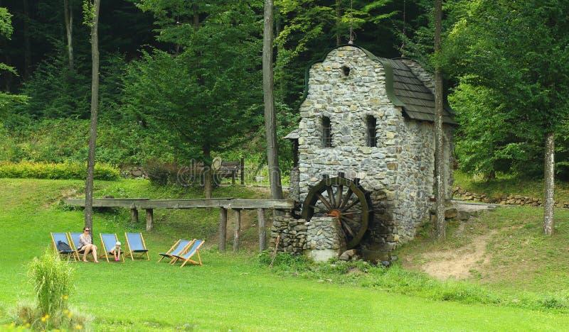 Os povos relaxam nos vadios perto do moinho de água velho foto de stock