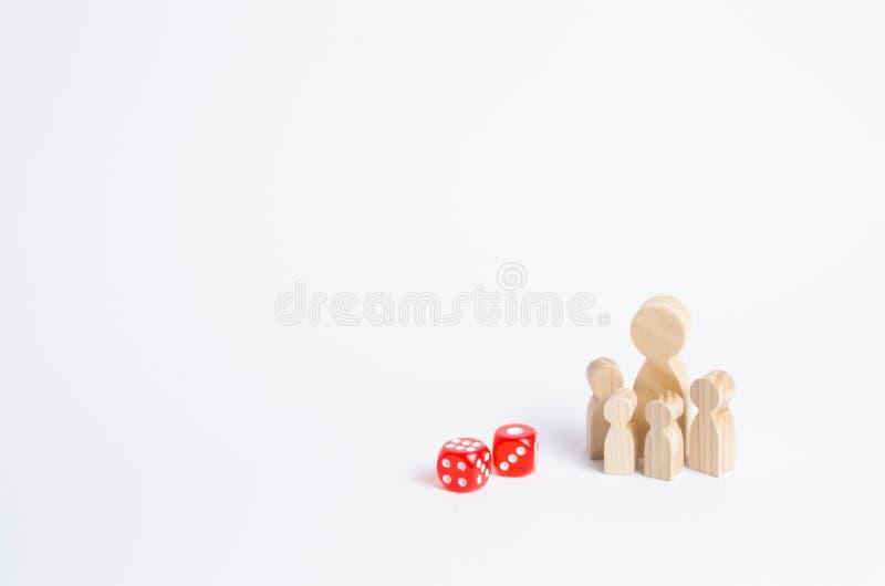 Os povos são dados próximos eretos A família está perto dos cubos dos dados O conceito do jogo, a dependência no jogo fotos de stock royalty free