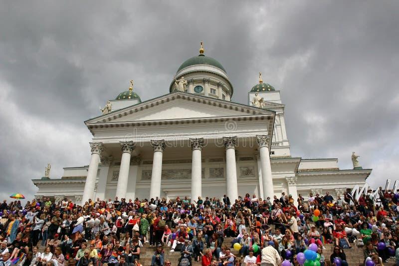 Os povos são recolhidos nas etapas da catedral de Helsínquia para esperar a parada de orgulho para começar foto de stock