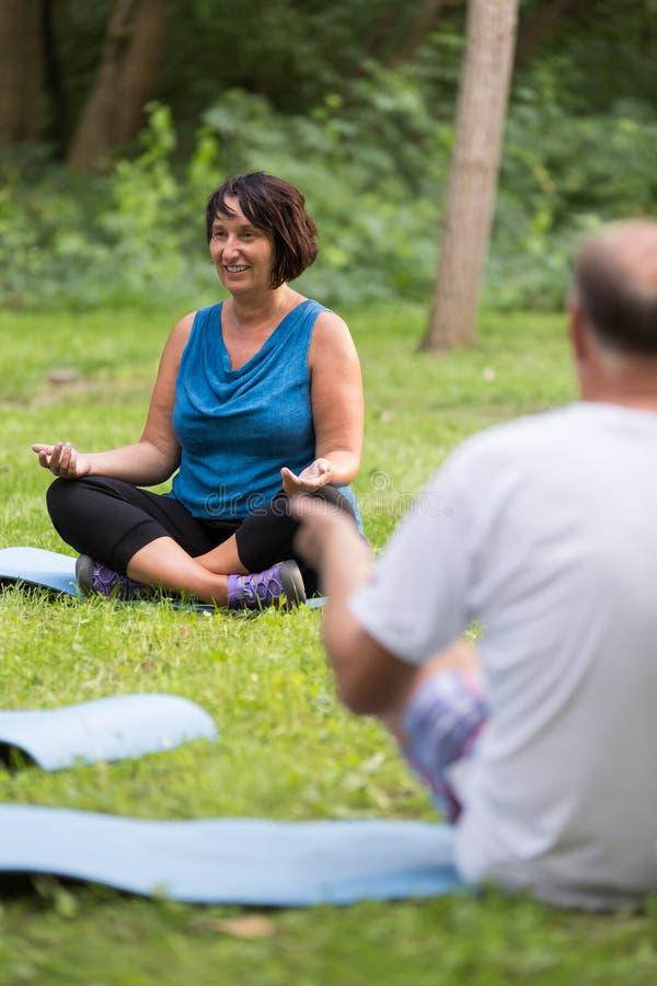Os povos superiores durante a ioga classificam em um parque imagens de stock royalty free