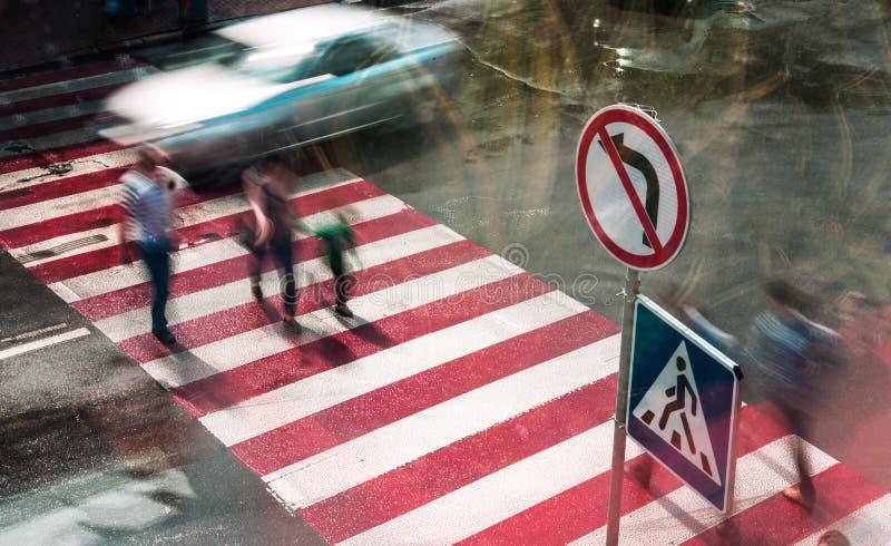 Os povos vão às estradas transversaas em um cruzamento pedestre Movimento borrado foto de stock royalty free