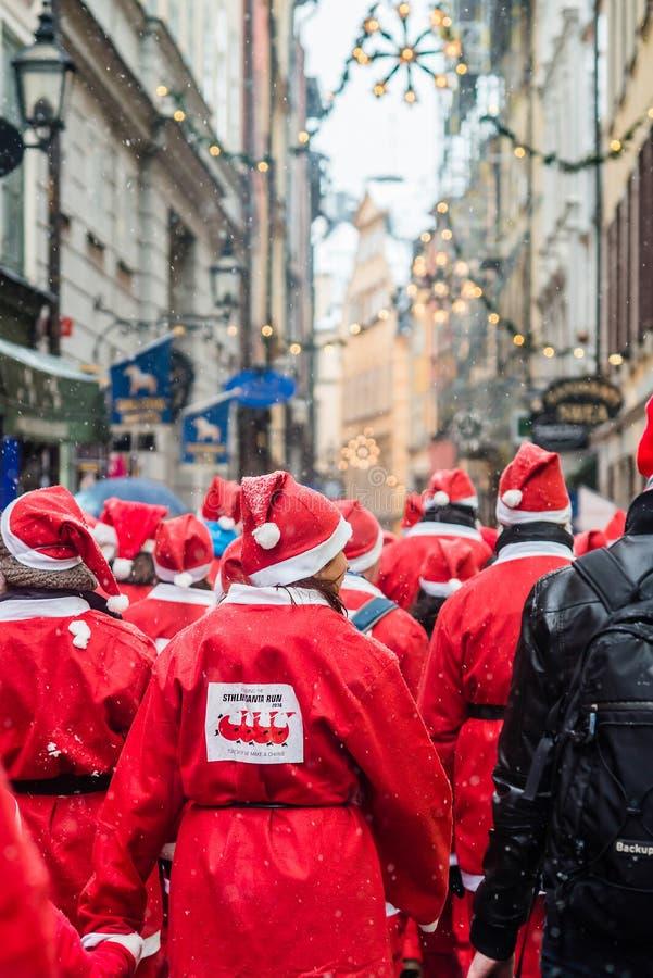 Os povos vestiram-se acima como Santa correm através da cidade velha de Éstocolmo, participando no evento Éstocolmo Santa Run da  imagens de stock