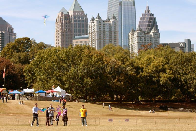 Os povos voam papagaios no parque contra a skyline da cidade de Atlanta imagens de stock