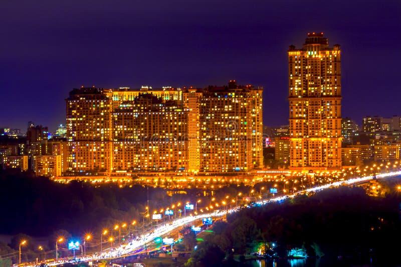 Os prédios altos de apartamentos são iluminados contra imagens de stock