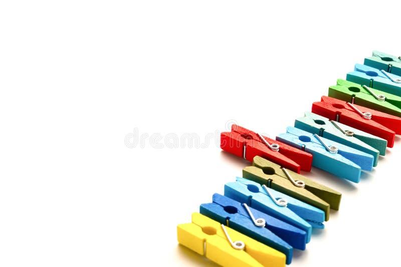Os pregadores de roupa de madeira coloridos com um colam para fora no fundo branco imagens de stock royalty free