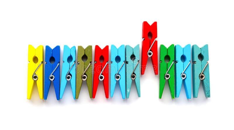 Os pregadores de roupa de madeira coloridos com um colam para fora no fundo branco fotos de stock