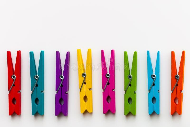 Os pregadores de roupa de madeira coloridos no fundo branco com cópia espaçam/conceito da diversidade imagem de stock